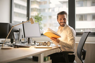 Smiling male business owner holding a book while working at office desk
