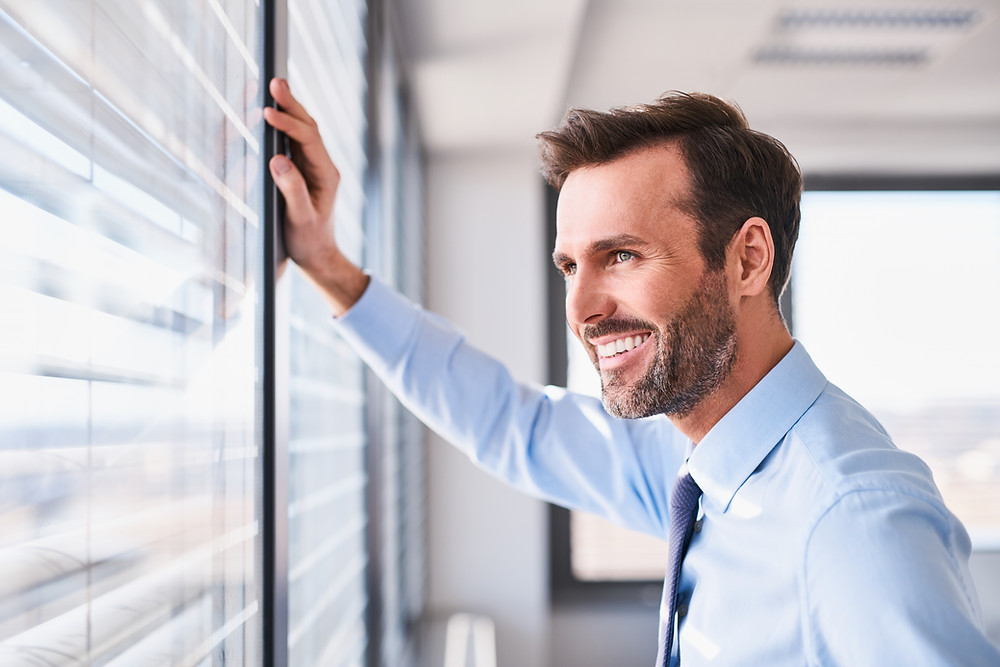 Happy and successful business owner in office looking out the window