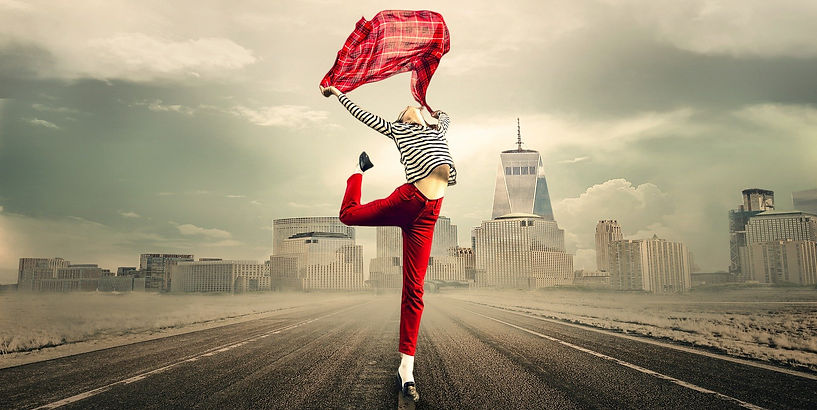 Female small business owner in red trousers and stripey top standing on an empty road in front of silver skyscrapers leaping in the air holding a red tartan scarf celebrating success