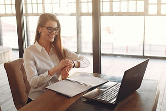 Smiling young female business owner checking time on wristwatch while working on laptop in modern workspace