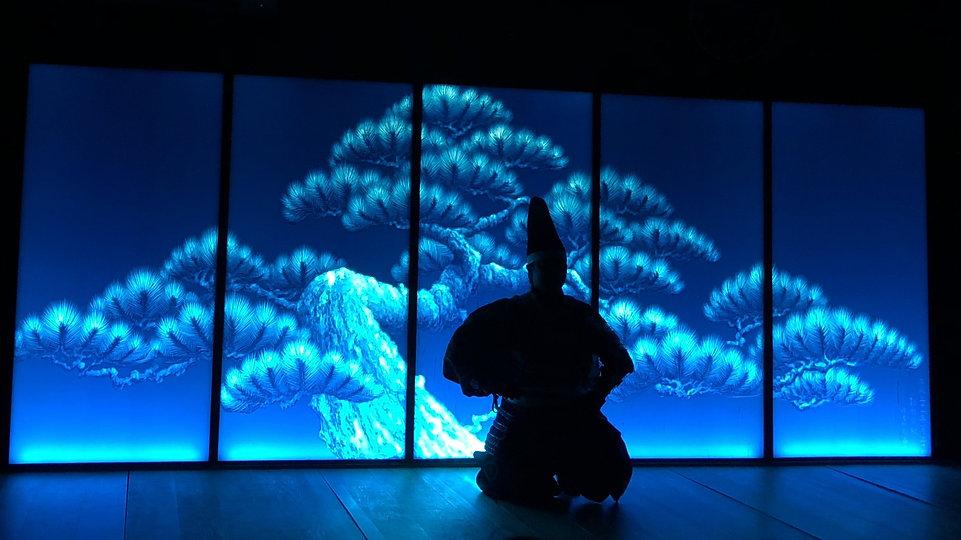 青い松の作品の前に座る狂言師の姿