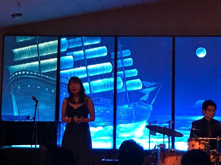 帆船と富士山を描いた青い大作品を背景にして歌う歌手とドラマーの姿