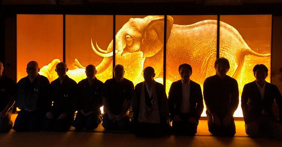 象を描いたオレンジ色の大作品の前に並んだお坊さん達。
