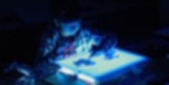 青く光る作品を制作する少女の姿。ワークショップ。