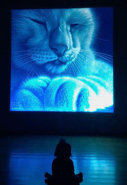 青く光る猫の大作品の前に座る赤ちゃんの姿