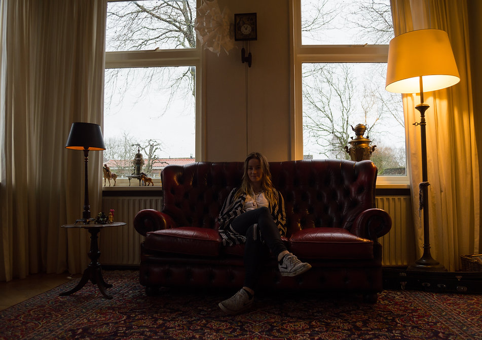 girl sitting on couch inside a Dutch home