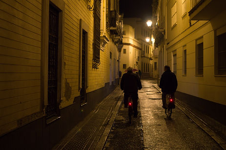 People riding bikes in the streets of Seville, Spain at night