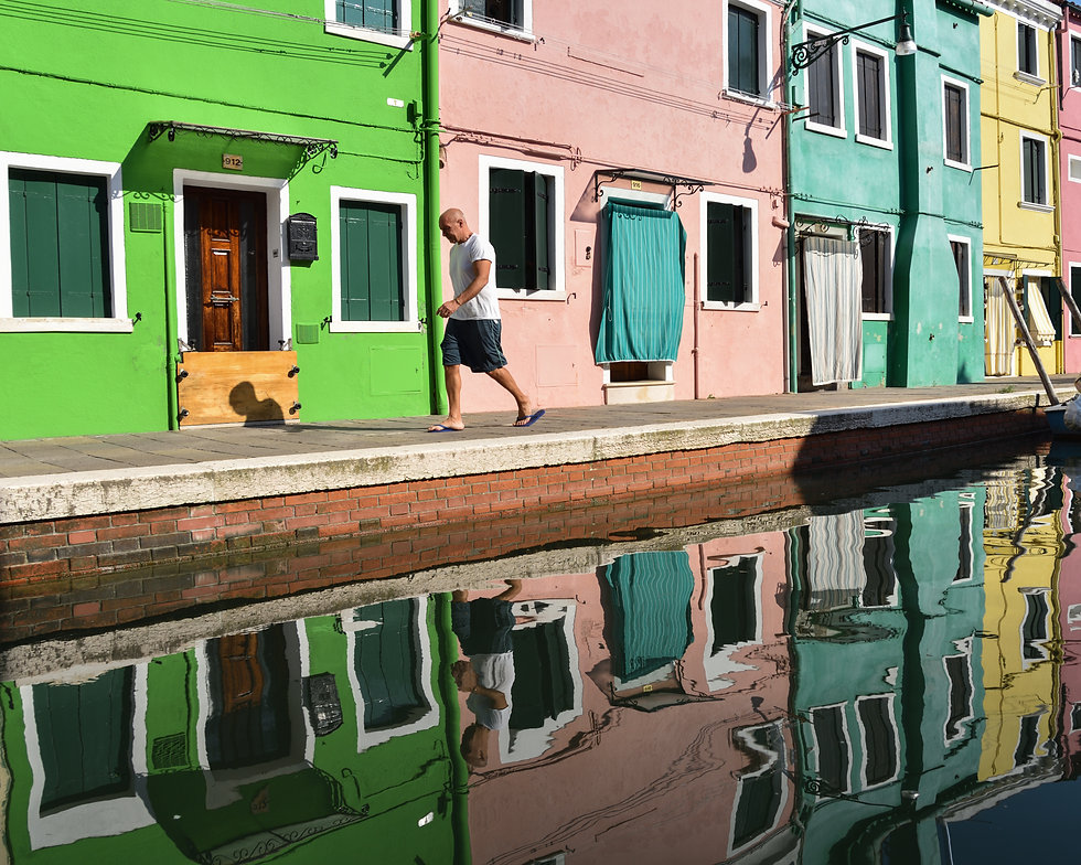 Man walking in front of colorful houses in Burano, Venice, Italy