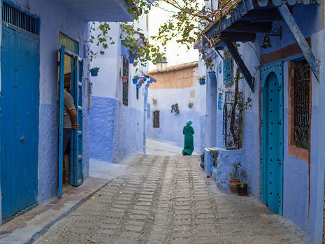 people in a blue alley in Chefchaouen, Morocco