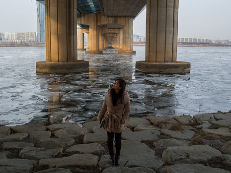 Woman standing in front of frozen river in Seoul, South Korea