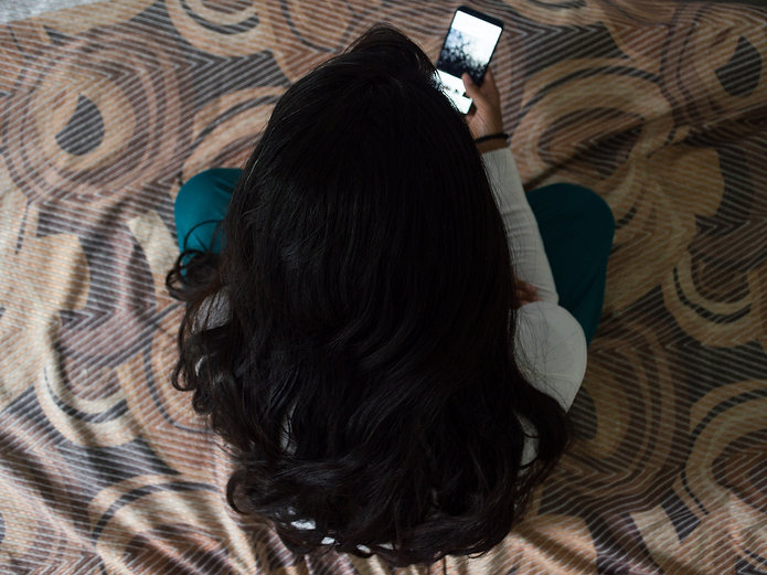 woman sitting on the bed with a phone