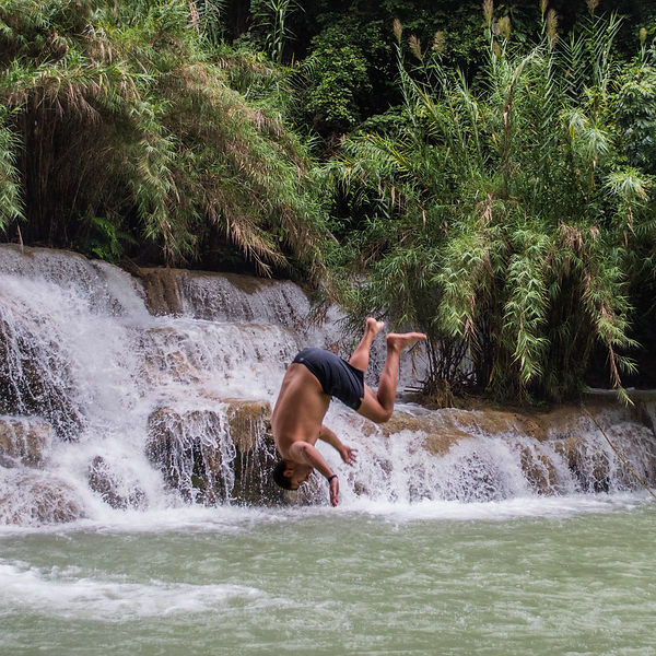 A man jumping into the waters of Kuang Si waterfall in Laos