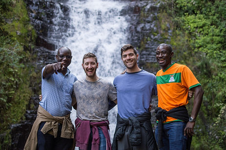 Four guys in front of a waterfall