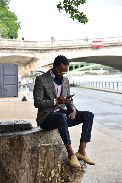 Fashionable man sitting by the Seine in Paris, France