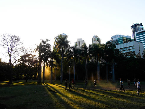 playing soccer at sunset in a park in Brisbane