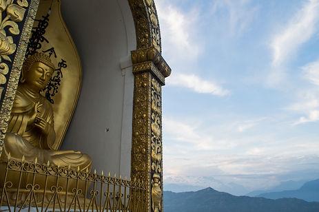 A golden Buddha statue at a stupa in the mountains around Pokhara, Nepal