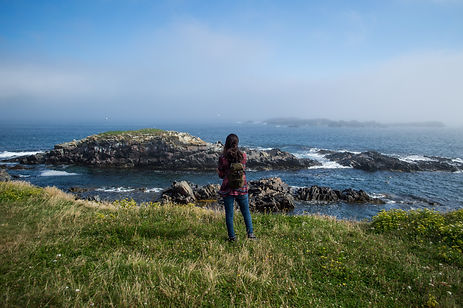 A woman standing on cliffs in Newfoundland, Canada