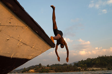 a man head diving from a boat into Lake Kivu in Rwanda