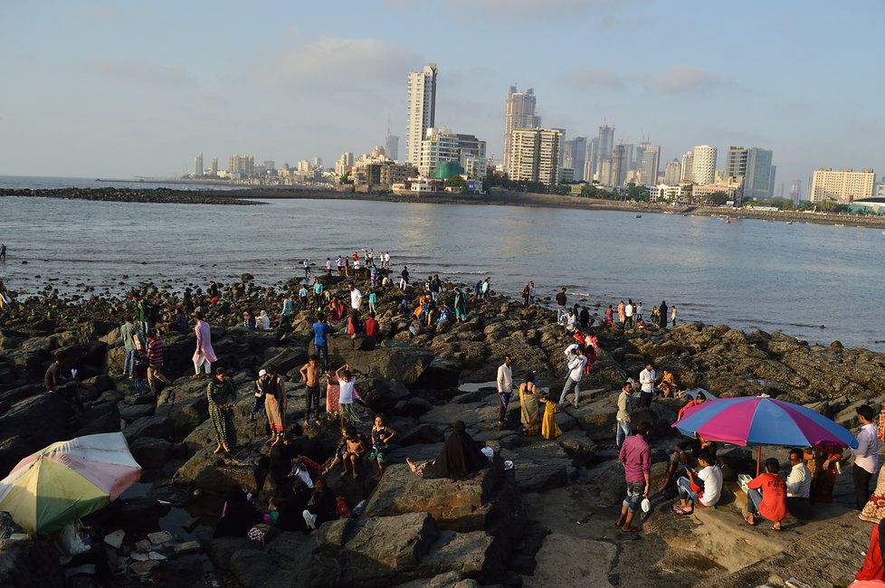 People gathering on rocks by the sea at Haji Ali Dargah mosque in Mumbai, India
