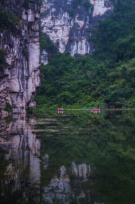 Lime stone formations, people rowing and reflection in Tam Coc, Vietnam