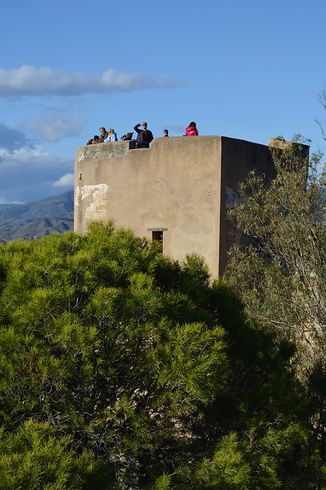 Tourists looking out from a fortification in Malaga, Spain