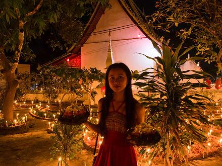 Woman with candles for the Boun Lai Heua Fai lantern festival in Luang Prabang, Laos
