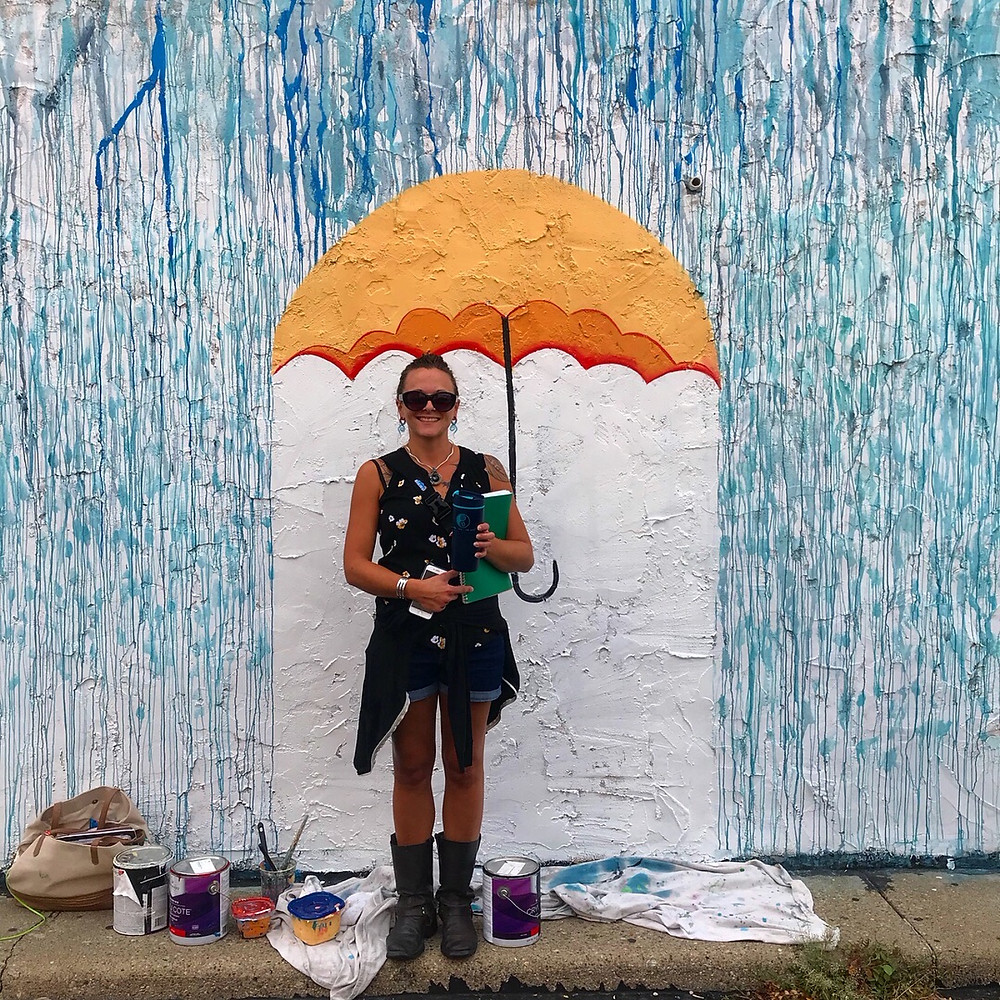 A woman posing under a painted umbrella, with painted raindrops falling all around her, part of a mural in Peoria, Illinois.