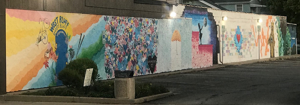 Brightly colored murals featuring hearts, umbrellas, bears, plant life, and words of positivity and love, located in an alley near One World Cafe in Peoria, Illinois.