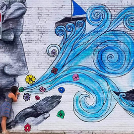 Immigrant mural stone lady blowing the wind and the water in Peoria, Illinois painted by Jessica McGhee Hey Lola
