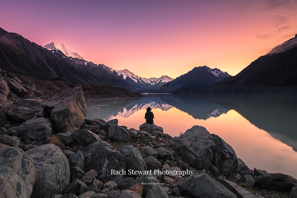 Tasman Lake sunrise with person Mount Cook