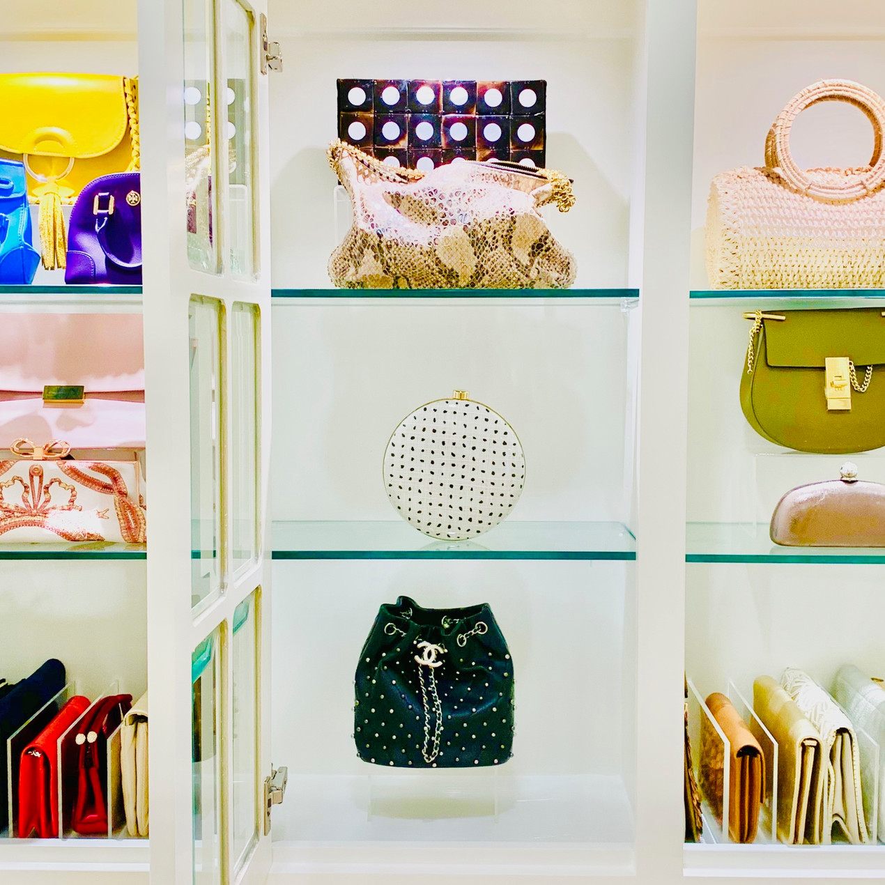 Closet organization by Jenny Dietsch at Getting it Done Organizing | Bags and purses on display in bright closet.
