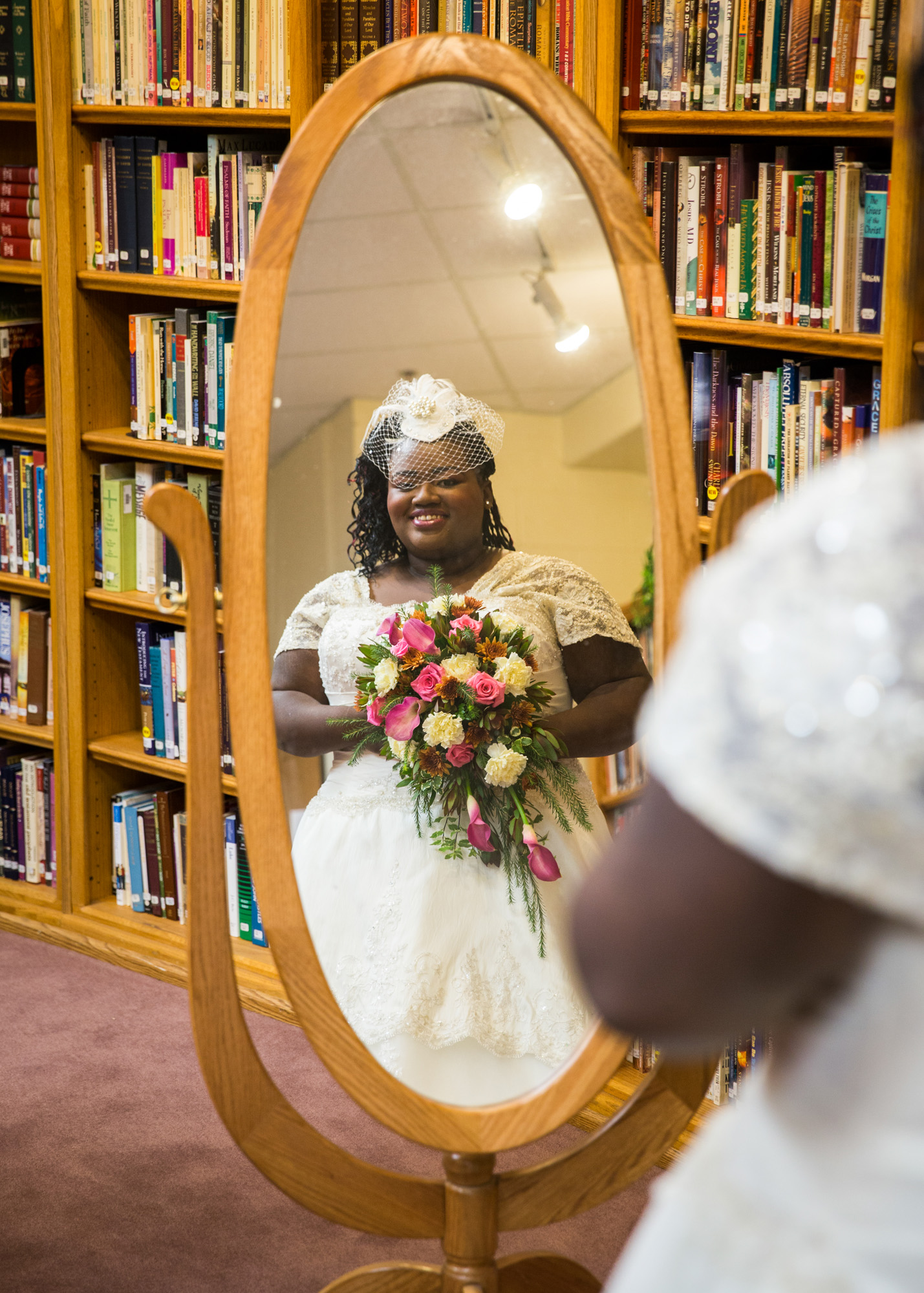 Bride with birdcage veil in mirror