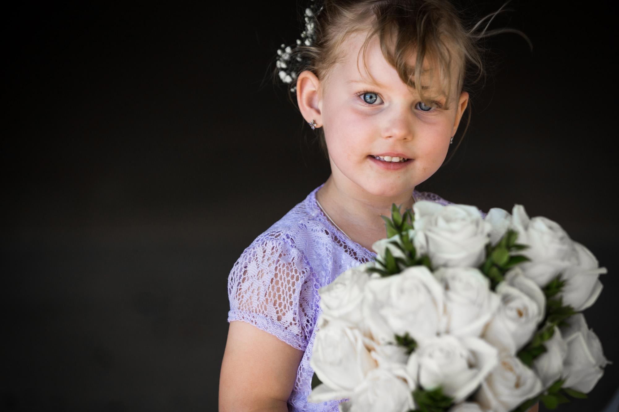 flower girl holding brides bouquet