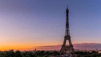 Paris s'éveille et la Tour Eiffel est baignée des premières lumières du jour.