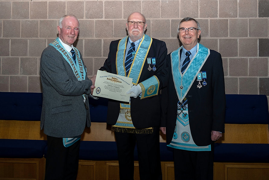 W.Bro. Bill Patterson, accompanied by his cousin, W.Bro. Jim Porter,  being congratulated by the Worshipful Master, W.Bro. Lee Burnside on receiving his 50-year Jewel and Certificate.