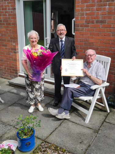 Worshipful Master, W.Bro. Joe Corr presents W.Bro Frank McNeice with his 65th Year Certificate and his wife Connie with a bunch of flowers.