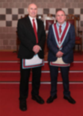 V.W.M. John McIlwaine accompanied by the Installing Officer, Bro. Simon Lusty.