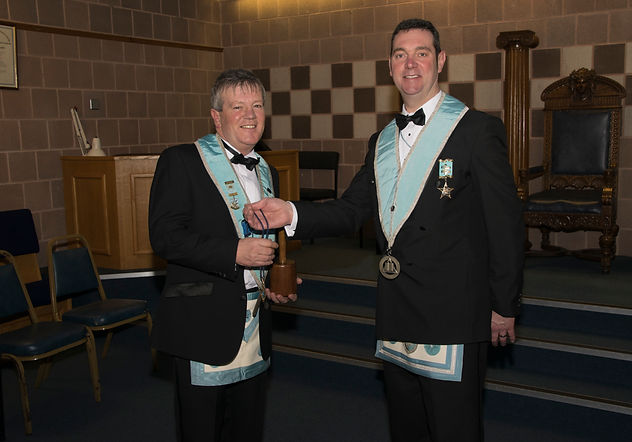 Wor. Bro. Stephen Bell, IPM presents the incoming Worshipful Master of Abbey 180, Terry Moore with the Lodge Jewel.