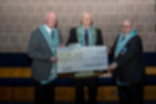 Worshipful Master, W.Bro. Lee Burnside accompanied by Hugh Blair presents a cheue of £485 to R.W.Bro. Bobby Spiers for £485 on behalf of the Grand Masters Festival, Vision 2020.
