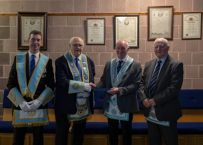 Worshipful Master Lee Burnside presents W.Bro. Scott PPGLI with a replica trowel on his retirement as a Provincial Grand Lodge Inspector. Accompanied by V.W. Bro. Stevie Bell and R.W. Bro. Bobby Spiers.