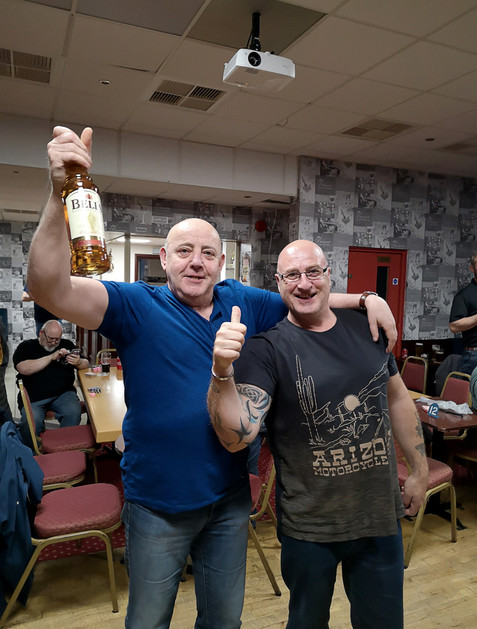 W.Bro. Houston, the winner of Pitch the Coin, holding his prize, a bottle of Bells.