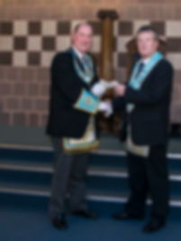 Worshipful Master Terry Moore presents the R.Worshipful Provincial Deputy Grand Master with a cheque for £   towards the Provincial Grand Lodge of Antrim Hospice bedroom equipment appeal .