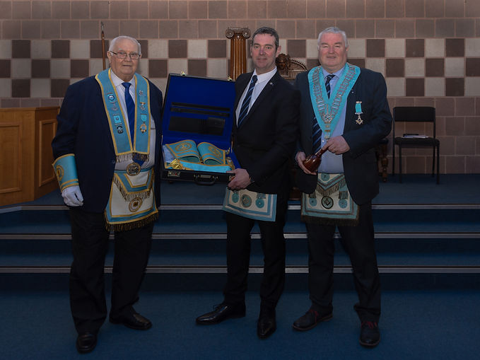 A proud W.Bro. Stevie Bell accompanied by W.Bro George Burnside showing his Provincial Grand Senior Warden regalia to W.Bro. Bobby Scott, PGLI.