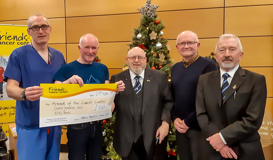 """Worshipful Master, W.Bro. Lee Burnside accompanied by Bto. Hugh Blair, W.Bro. Alan Hunter and W.Bro. Joe Corr presents a cheque for £750 to Dr. Mitchell at the """"Friends of Cancer Centre""""."""