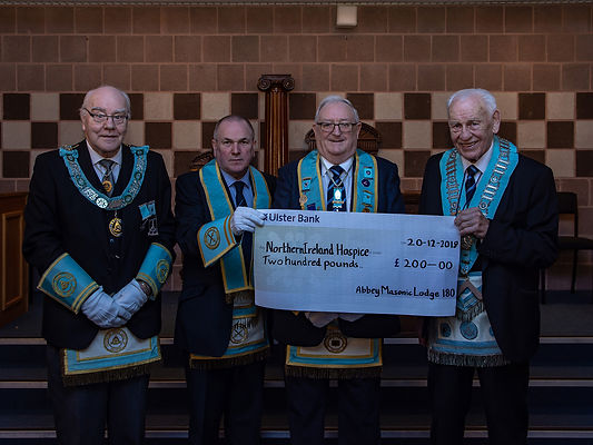 W.M. Neil Ritchie accompanied by R.Wor. Bro. J.O. Dunlop, Provincial Deputy Grand Master, presents a cheque for £200 to W. Bro. John McIlwaine PPGLIG and W. Bro Foster Clyde PPGLI , who are receiving it on behalf of the Northern Ireland Hospice.