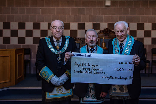 W.M. Neil Ritchie accompanied by R.Wor. Bro. J.O. Dunlop, Provincial Deputy Grand Master, presents a cheque for £200 to W.Bro. Joe Corr, who is receiving it on behalf of the Poppy Appeal.