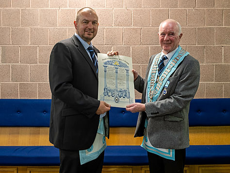 Worshipful Master, W.Bro. Lee Burnside congratulating Bro. Gareth Moody on receiving his                        Master Mason Certificate.