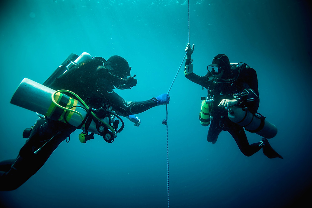 Two scuba divers with oxygen tanks and a safety line.