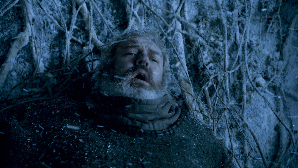 Hodor, character from the TV series Game of Thrones, holds back a door covered in vines and snow. He looks visibly distressed.