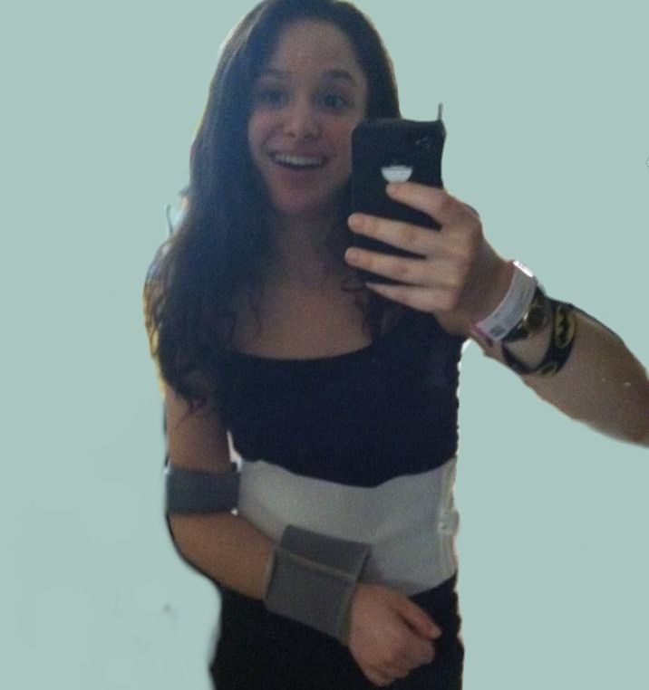 Me as a teenager, a pale thin white girl with brown hair, a wide but fake smile, a hospital bracelet, and an elbow sling that wraps around my waist. I am taking a mirror selfie.